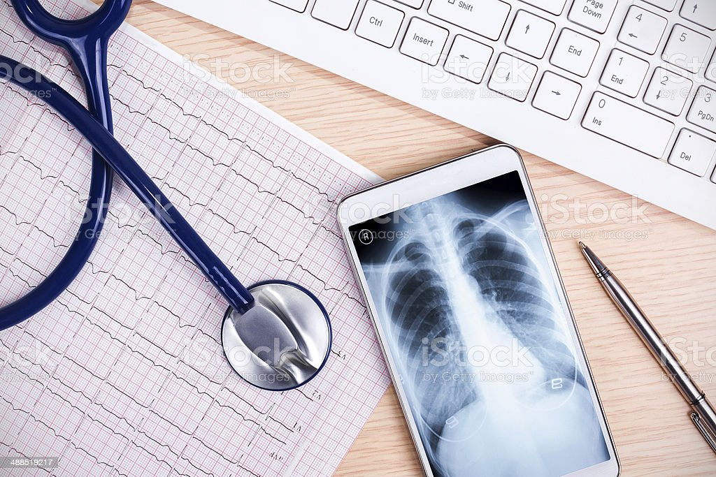 online medical service:X-ray and smartphone with stethoscope stock photo