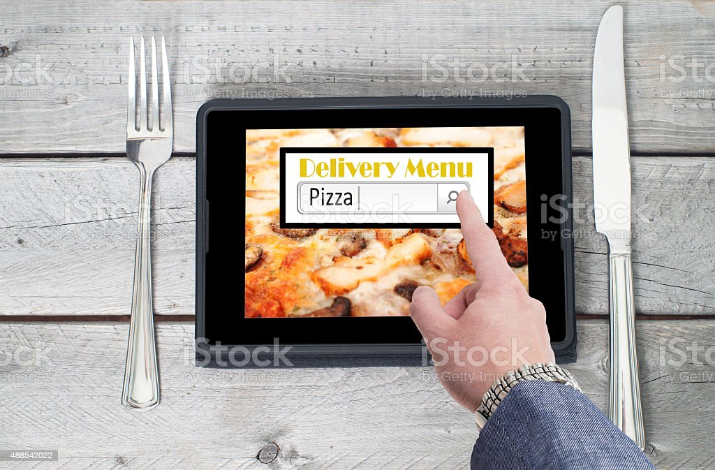 On-line pizza ordering and delivery concept with a digital table stock photo
