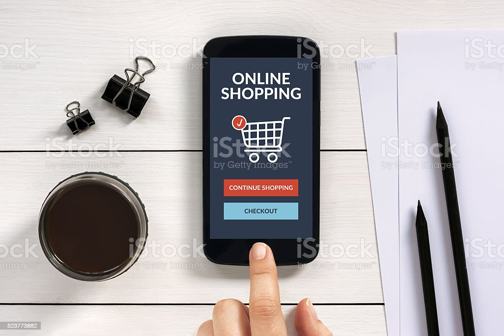 Online shopping concept on smart phone screen with office objects stock photo