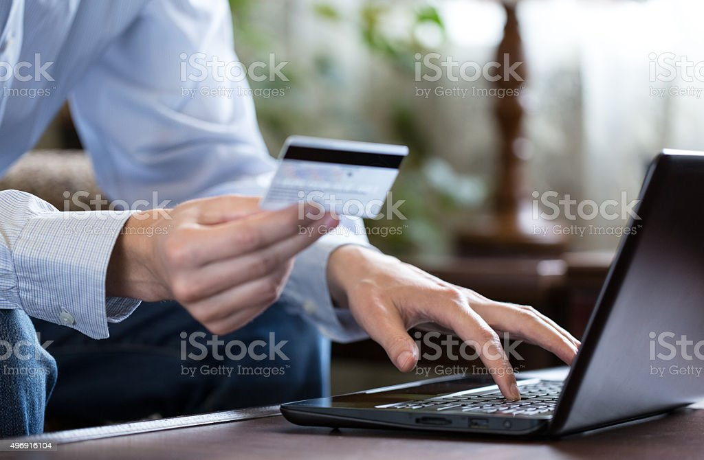 Online shopping. Young man buys in online shop. stock photo