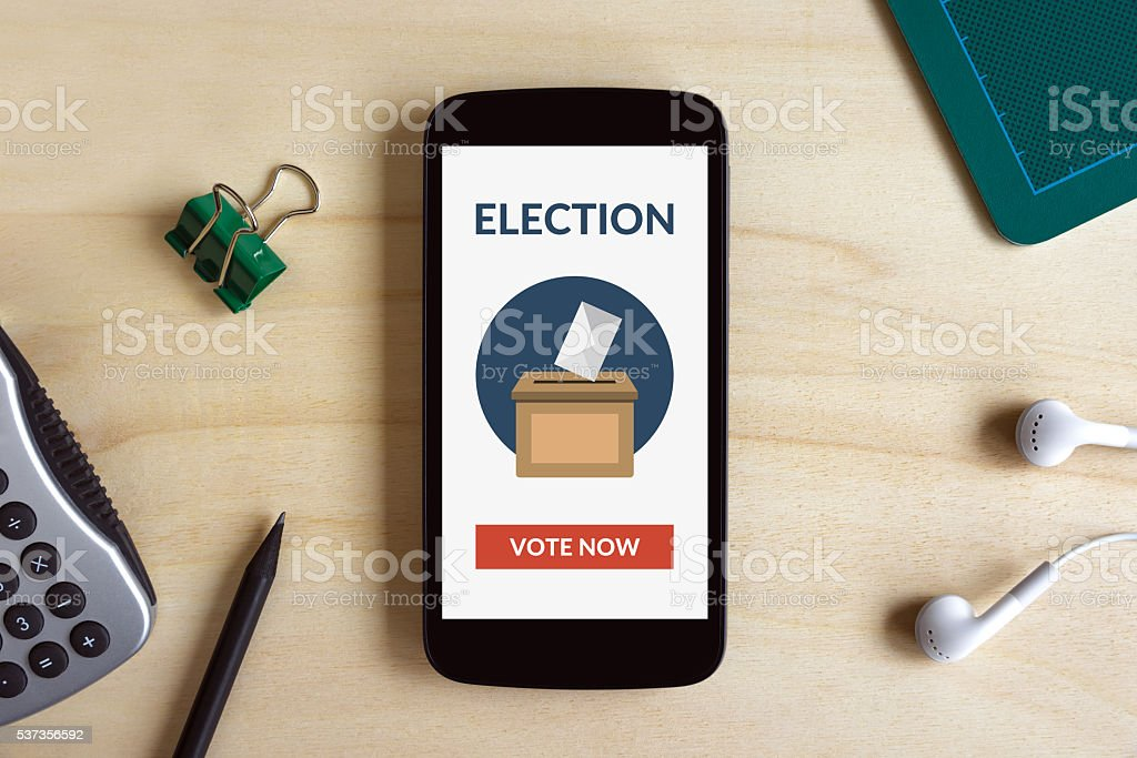 Online voting concept on smart phone screen on wooden desk stock photo