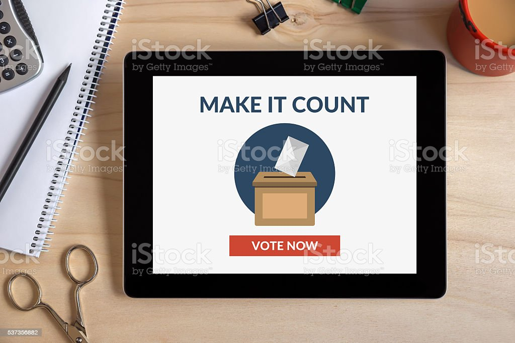 Online voting concept on tablet screen with office objects on desk stock photo