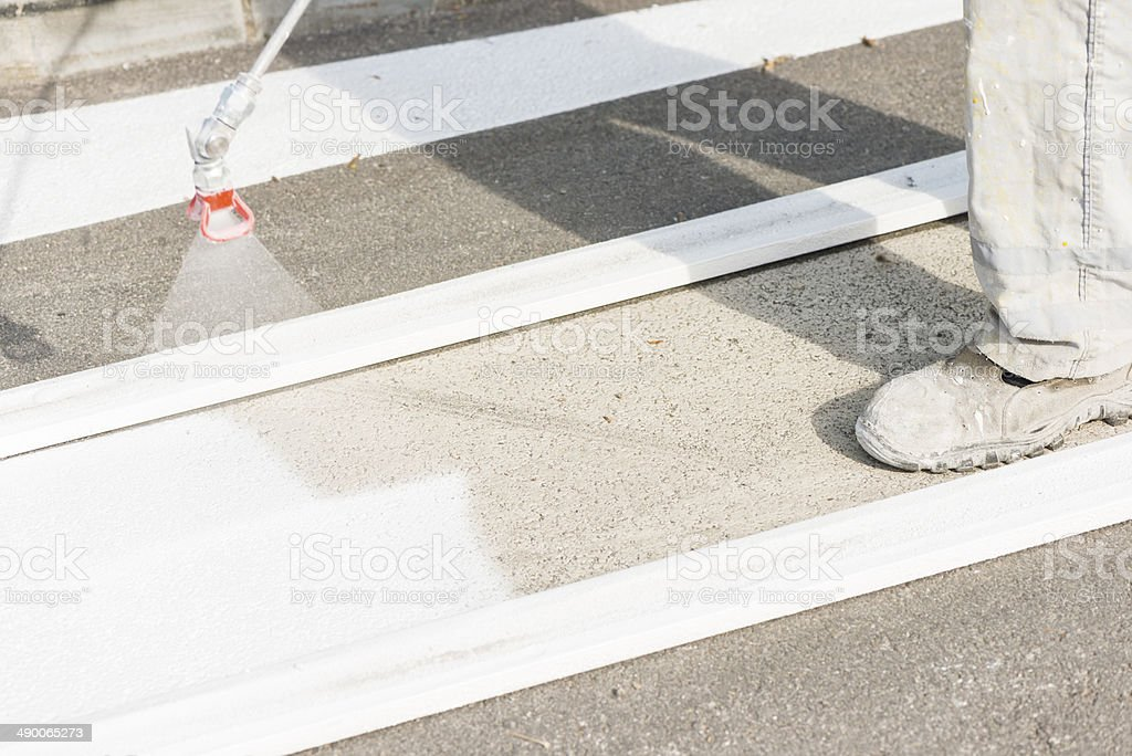 Only the feet are visible of someone spraying floor white. stock photo
