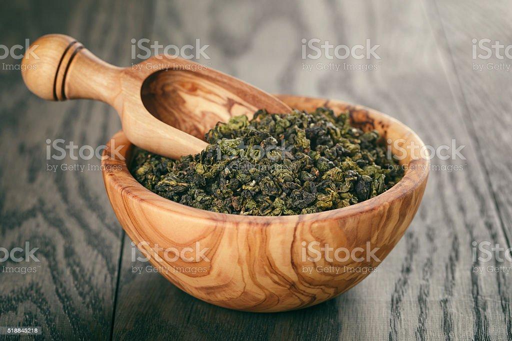 oolong green tea in wood bowl on oak table stock photo