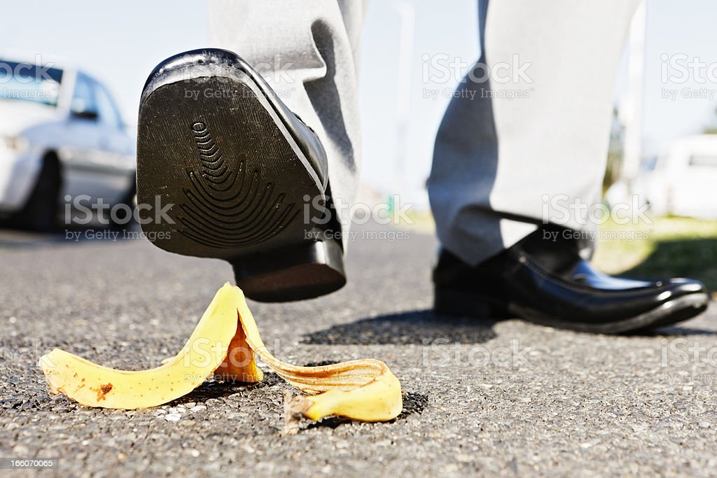 Ooops! Businessman about to step on banana peel stock photo