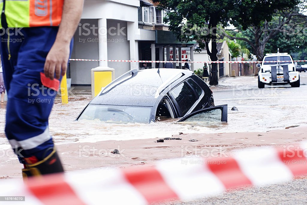 Oops! Car slipping into pothole in flooded street stock photo