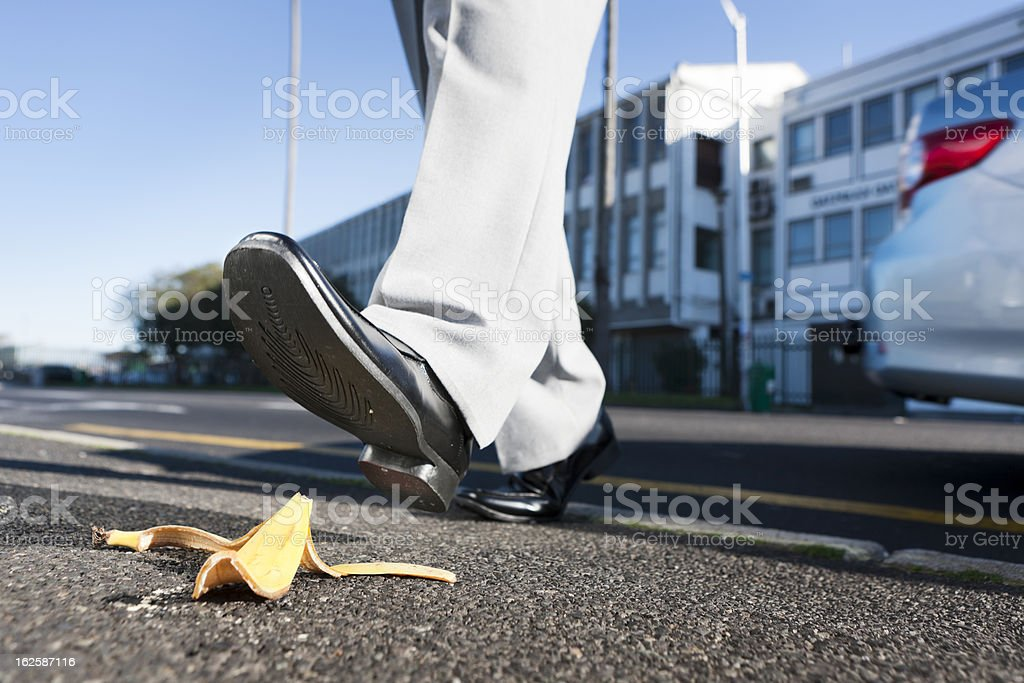 Oops! Smartly dressed man about to step on banana peel royalty-free stock photo