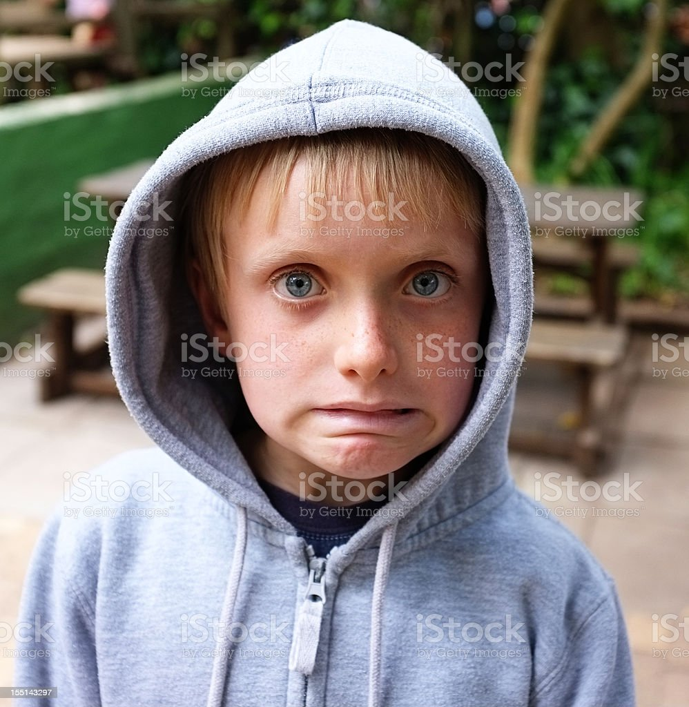 Oops! Young blond boy in hoodie is worried royalty-free stock photo