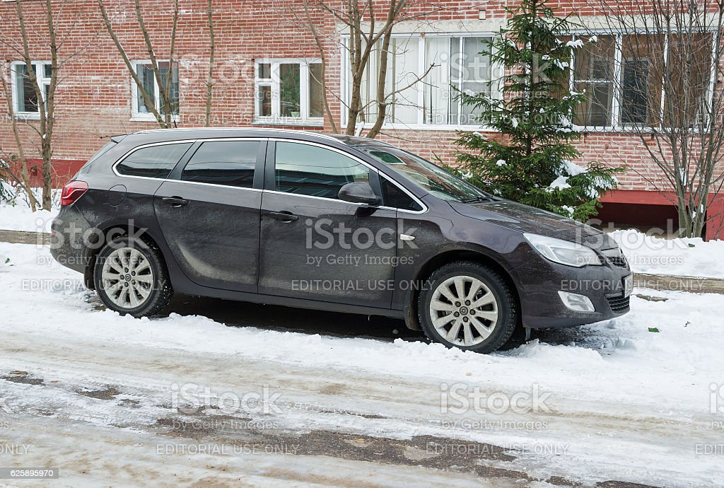 Opel Astra in winter near the house. stock photo