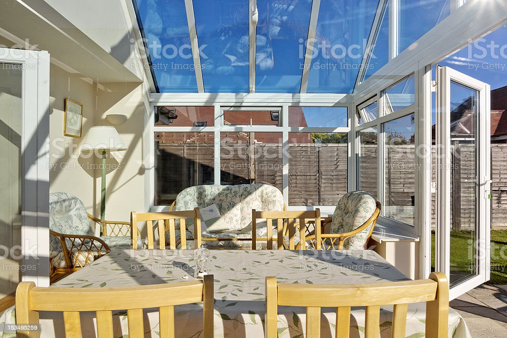 Open air conservatory with tables and yellow chairs stock photo