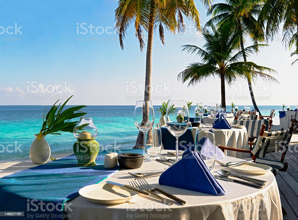 Open air restaurant table at beautiful blue water beach stock photo