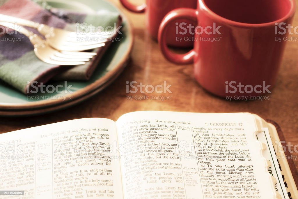 Open Bible and morning coffee on breakfast table. stock photo