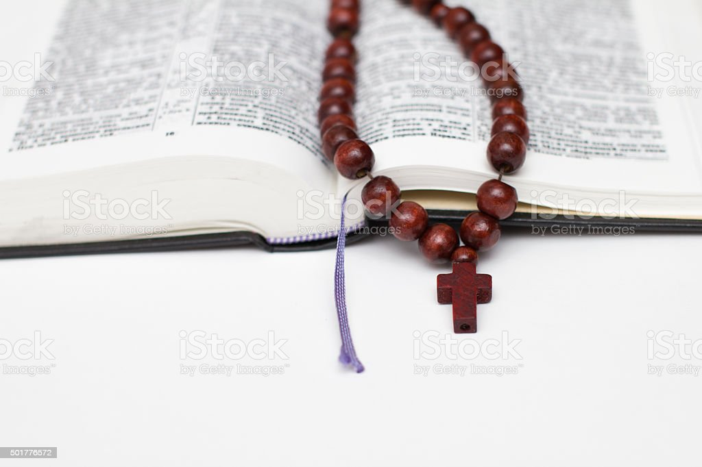 open bible book and rosary on white stock photo