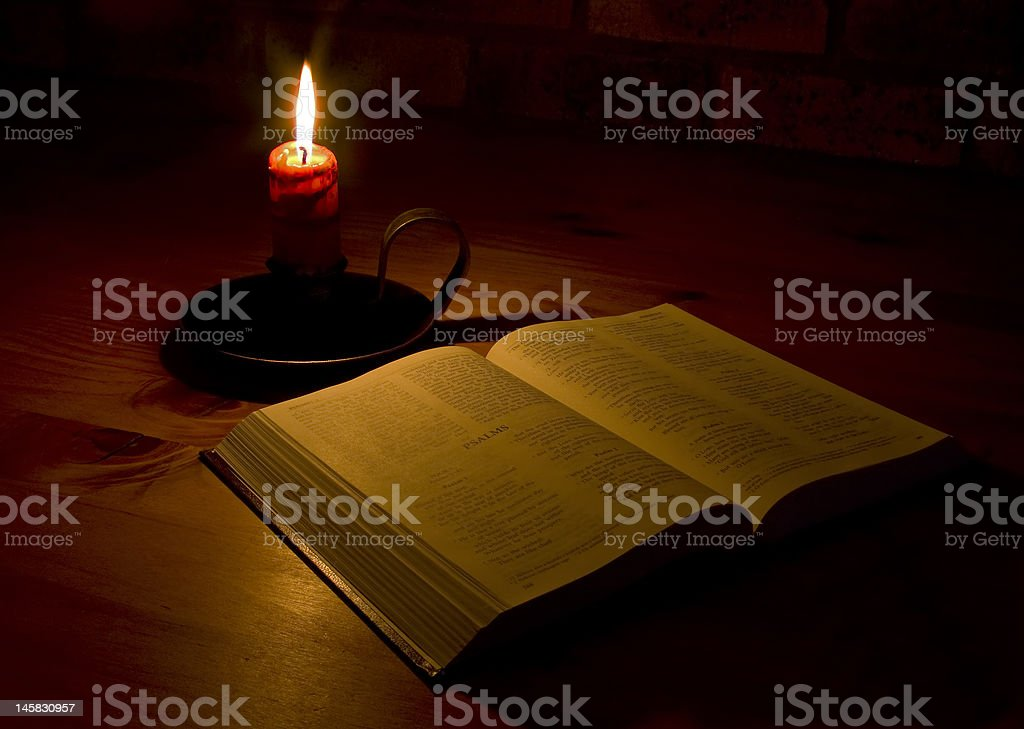 open bible by candle light stock photo