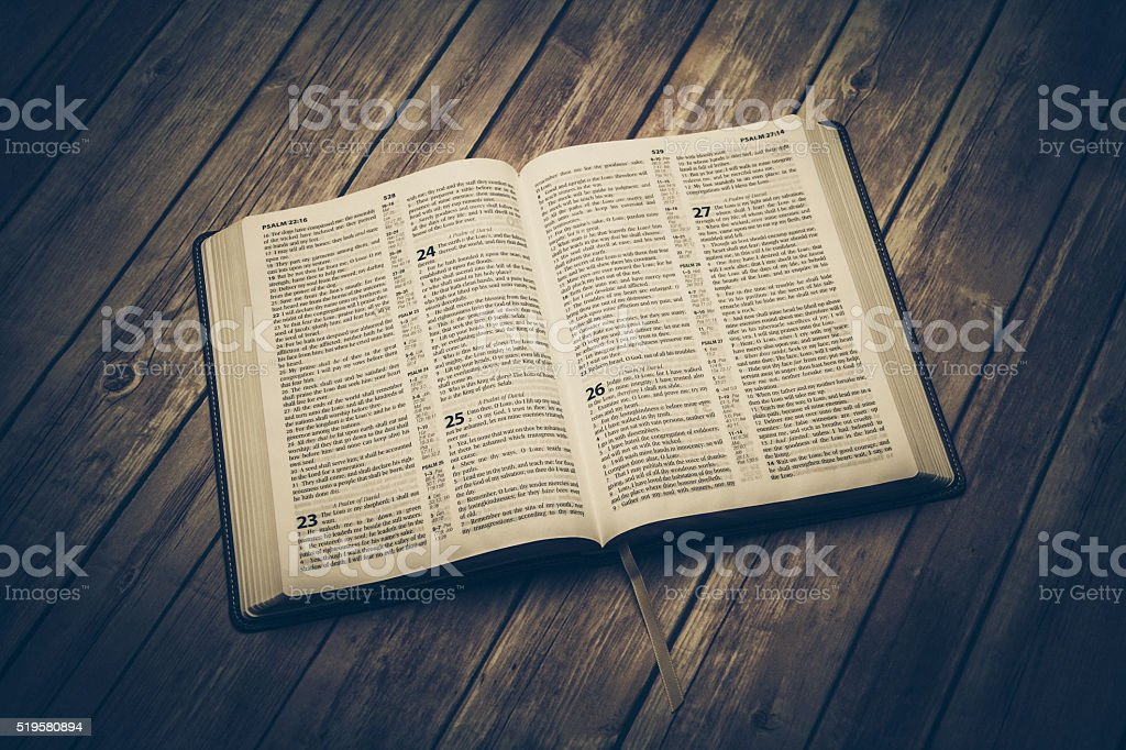 Open bible on a wooden table stock photo