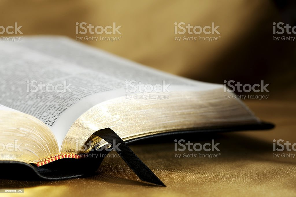 Open Bible on Gold Background stock photo