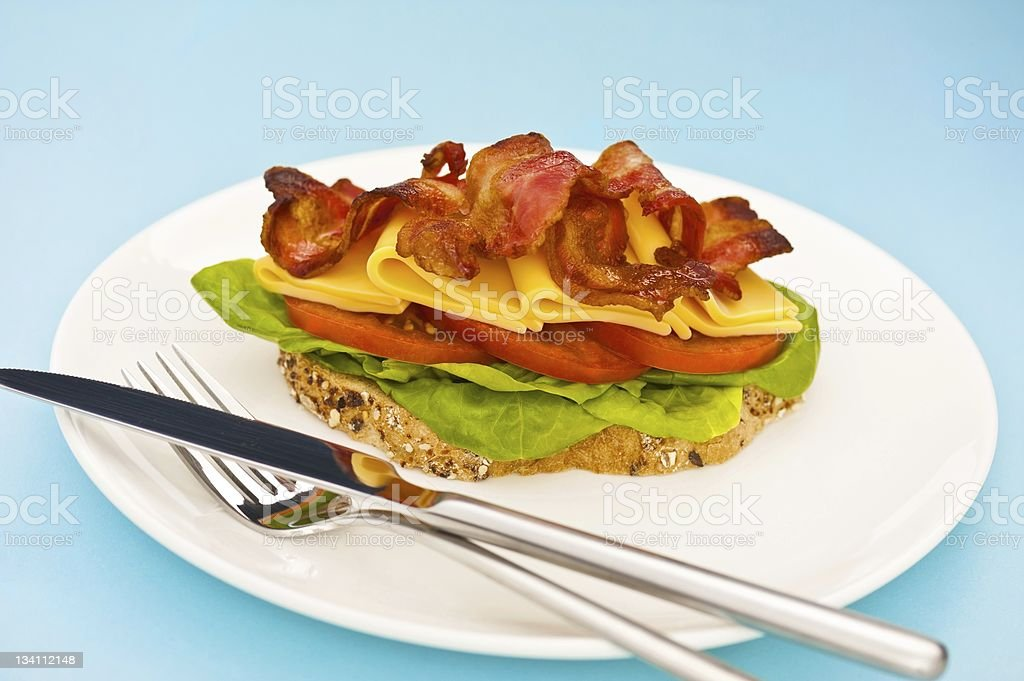 Open blt sandwich on a white plate with blue background royalty-free stock photo