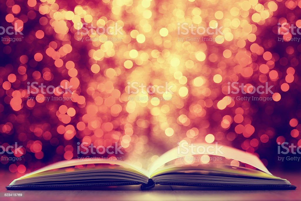 Open book against  defocused  lights abstract background stock photo