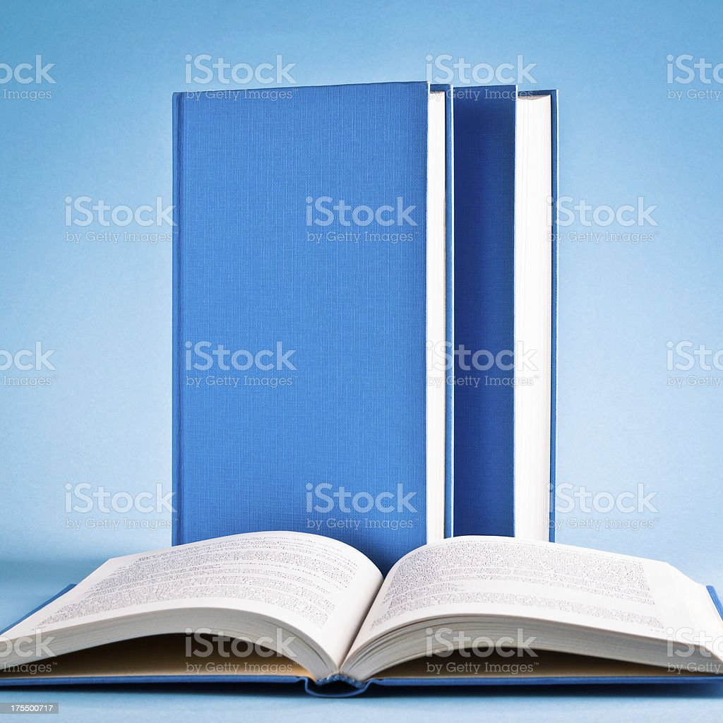 Open book and books in raw isolated on blue background royalty-free stock photo
