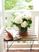 Open book and glasses on table next to flower pot