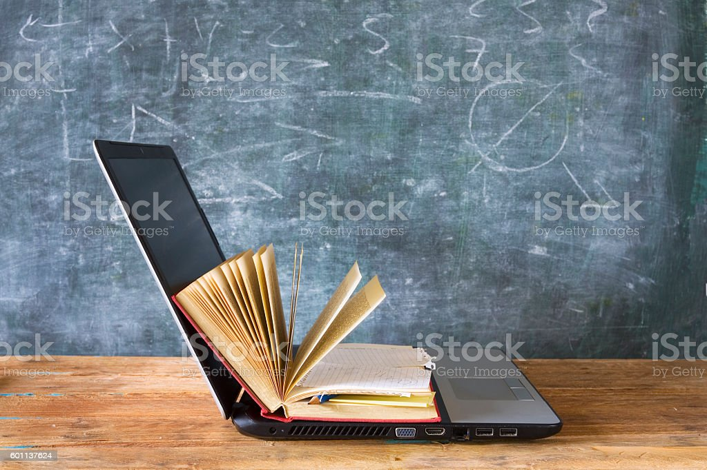 open book and laptop computer stock photo