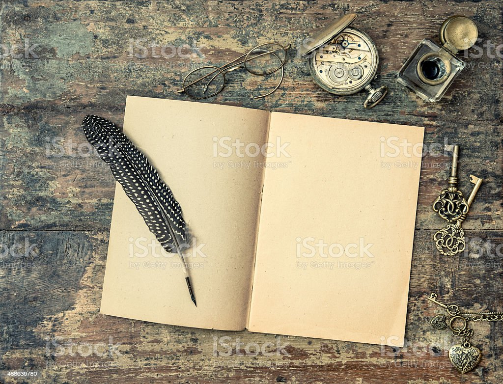 Open book and vintage writing accessories. Wooden texture background stock photo