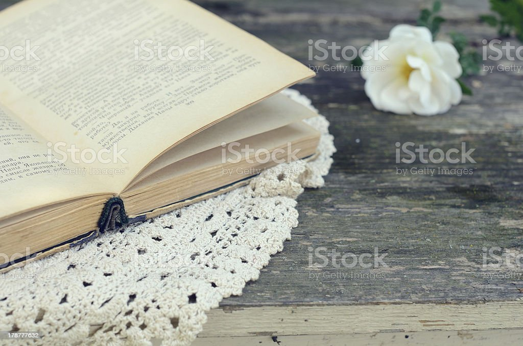 Open book laying upon lace doily on rusted garden table royalty-free stock photo