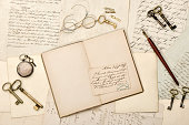 Open book, old letters, antique accessories. Vintage background