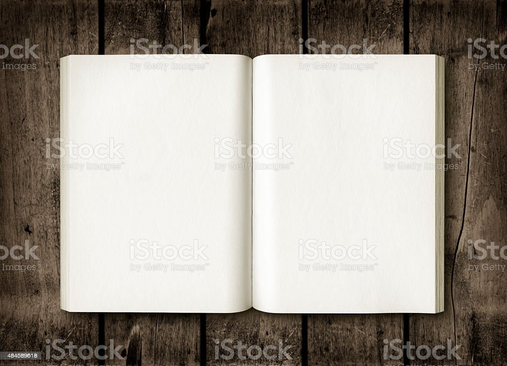 Open book on a dark wood table stock photo