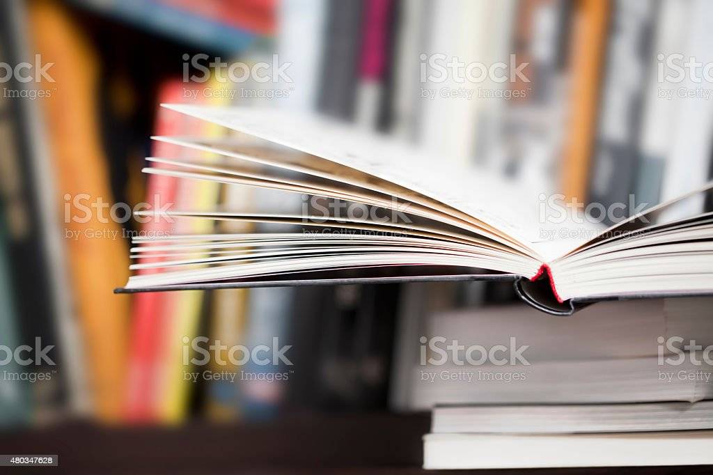 Open book on a shelf, many others behind. stock photo