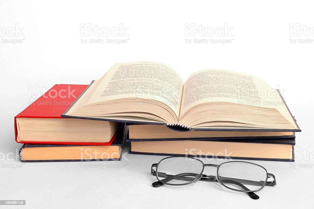 Open book on a stack of books with reading glasses royalty-free stock photo