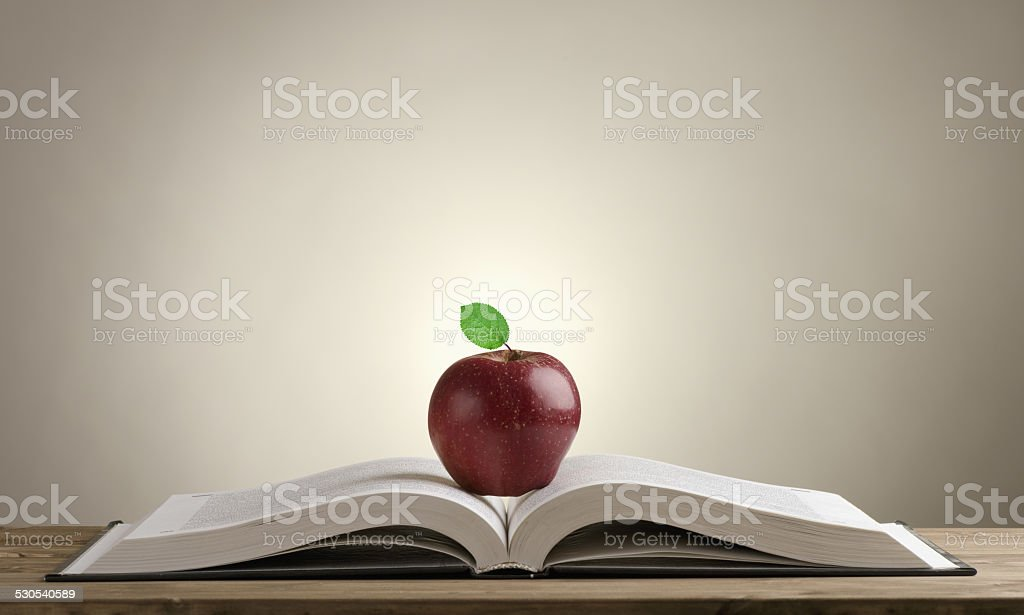 open book on a wooden Desk with a red Apple stock photo