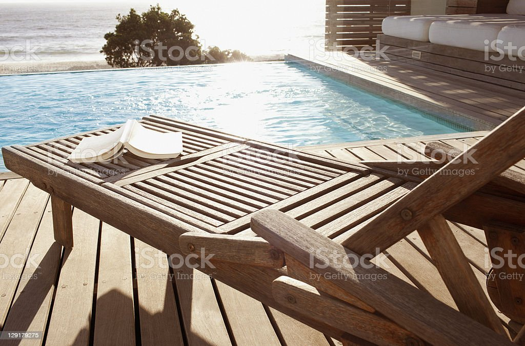 Open book on poolside lounge chair stock photo