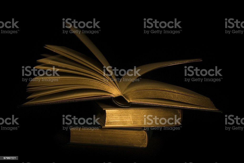 Open book on stack of closed ones - black background royalty-free stock photo