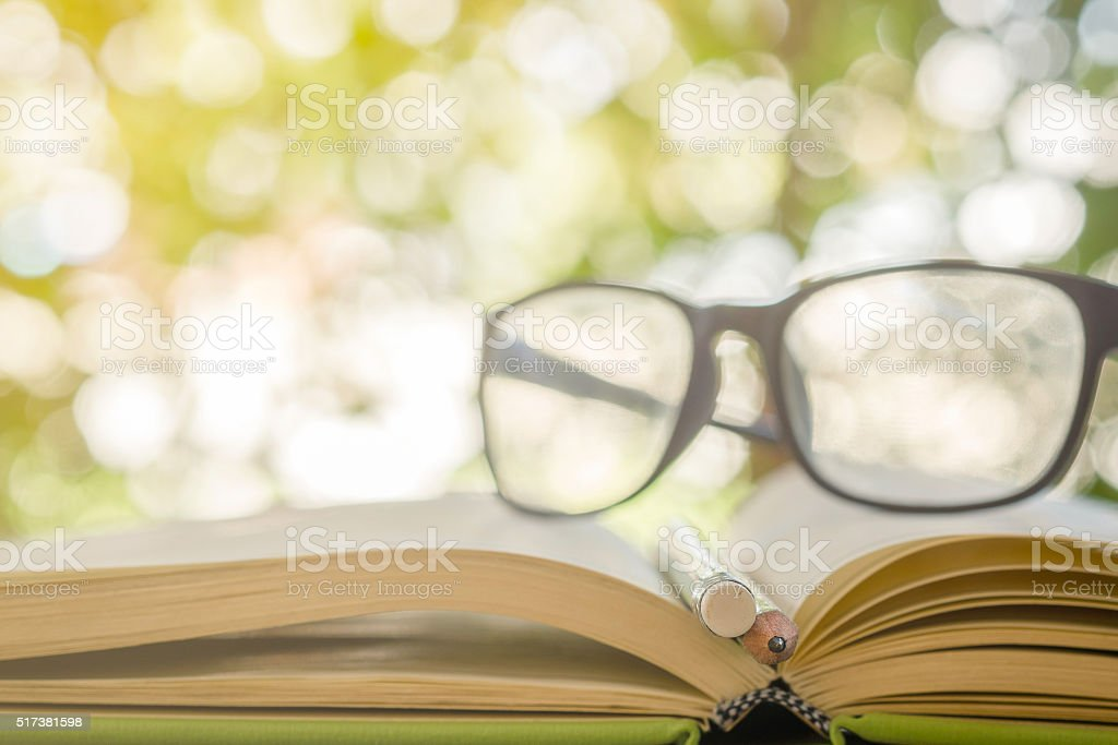 open book , pencil and glasses on bokeh background, stock photo