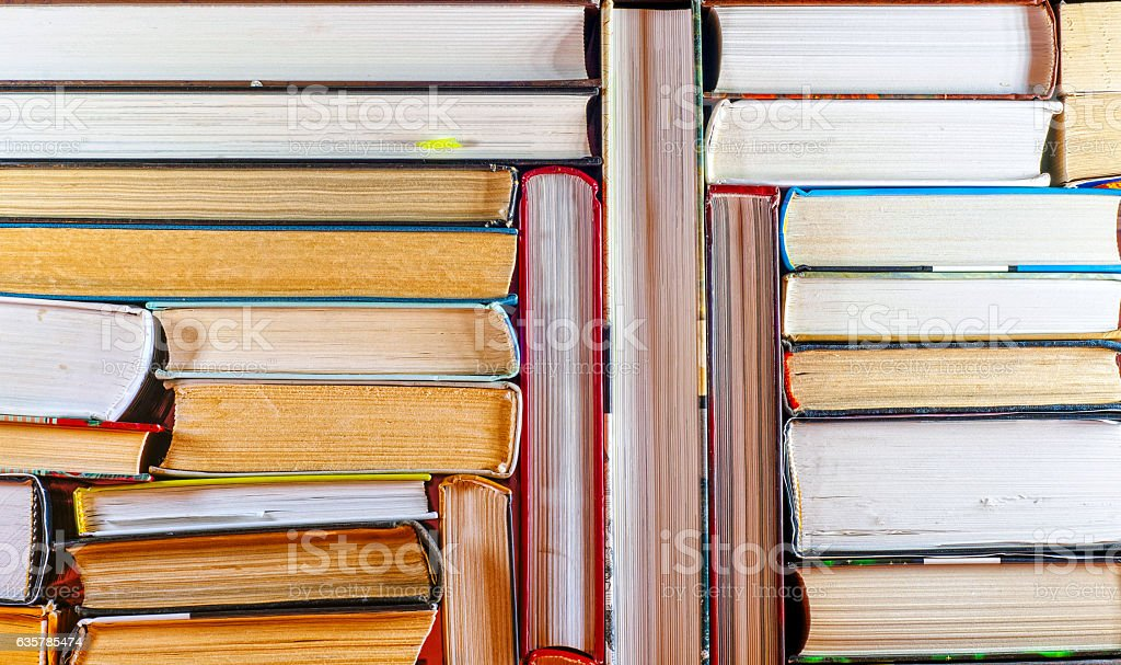 Open book, stack of colorful hardback books on light table. stock photo