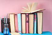 Open book, stack of colorful hardback books on light table.