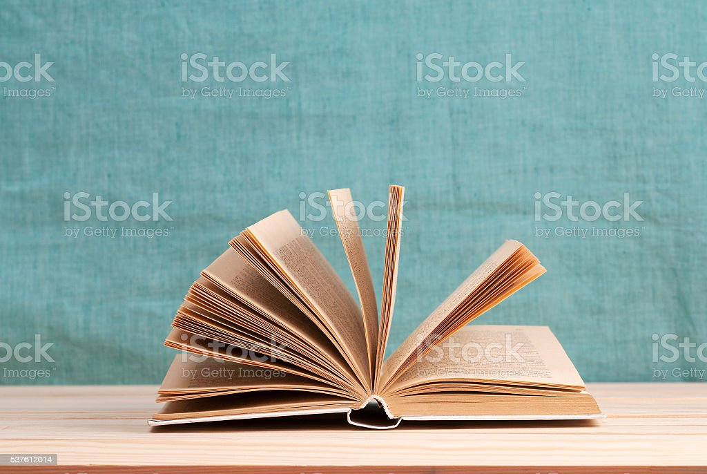 Open book, stack of hardback books on wooden table.  Back stock photo