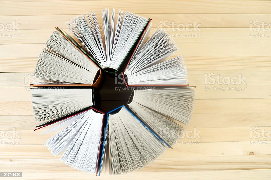 Open book, stack of hardback books on wooden table. stock photo