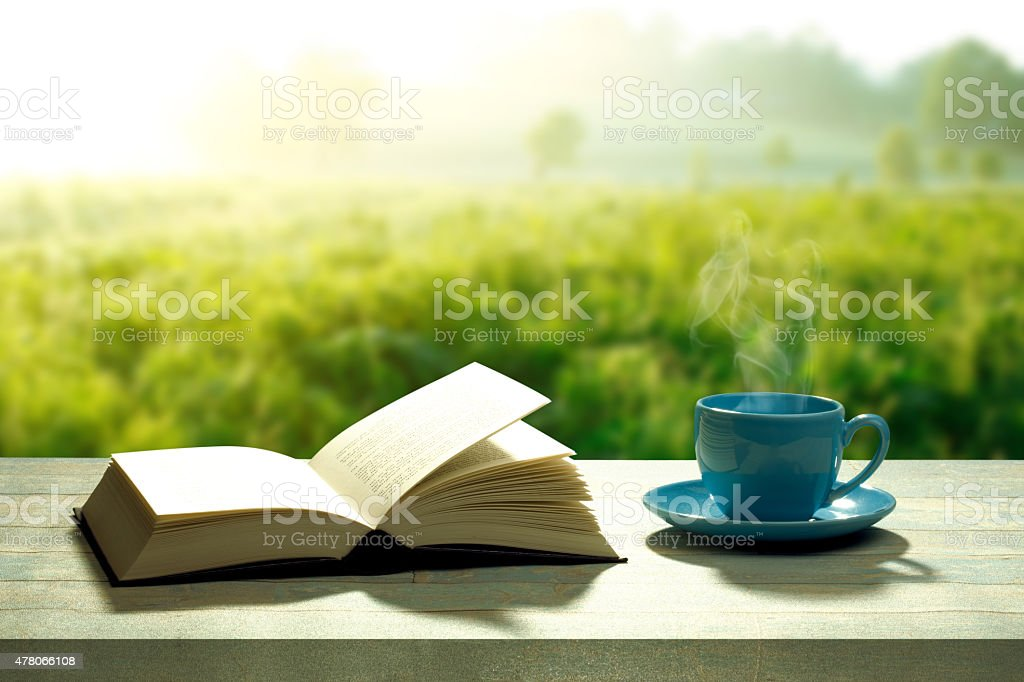 open book with a coffee cup and a wooden table stock photo
