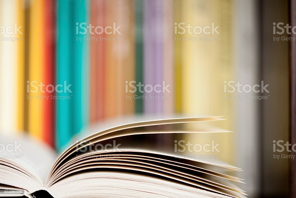 Open book with multicolored book spines background. stock photo