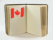 Open book with one page with Canadian flag, copy space