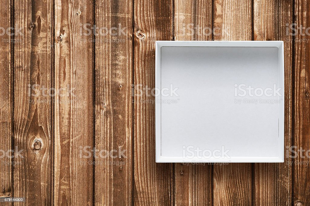 Open cardboard box on wooden background stock photo