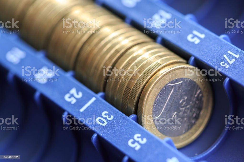 Open cash registrer containing many coins of euros in raw stock photo