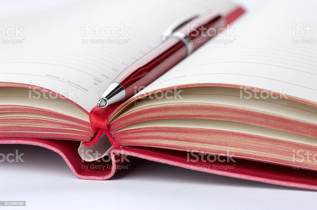 Open diary and pen red, closeup stock photo