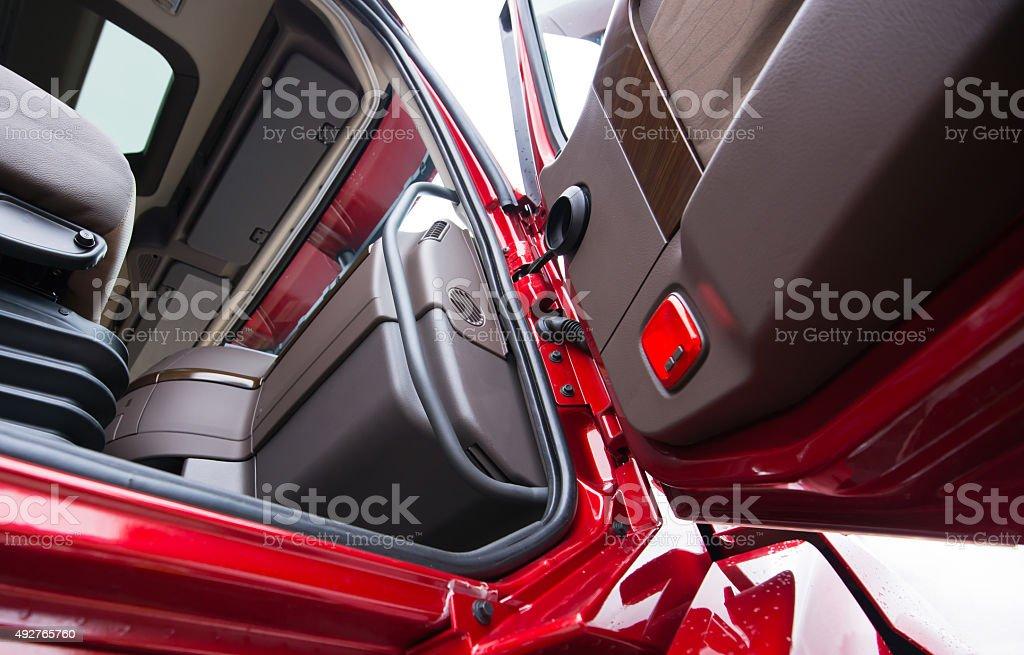 Open door of red semi truck with luxury brown interior stock photo