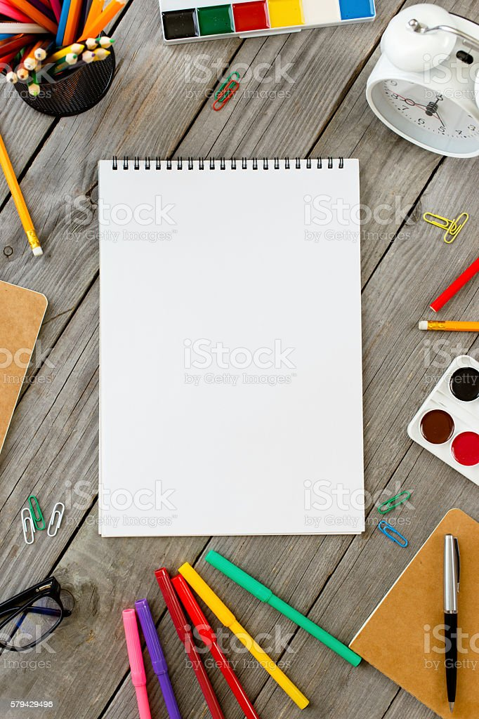Open drawing pad with school different supplies stock photo