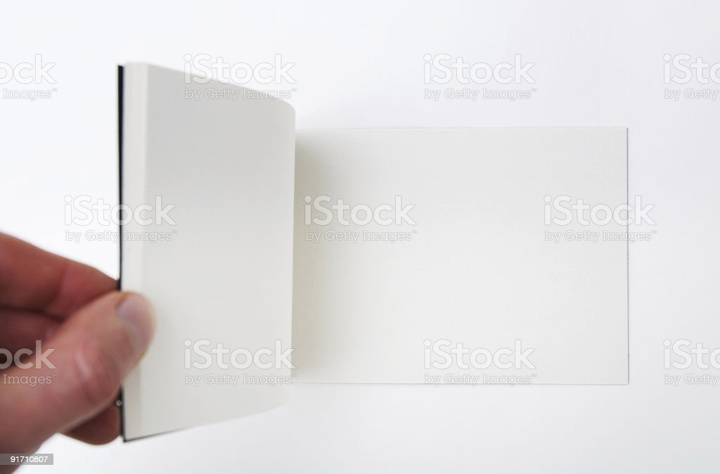 Open empty white book - Hand flipping pages. stock photo