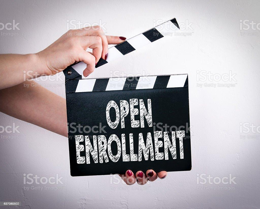 Open enrollment. Female hands holding movie clapper stock photo
