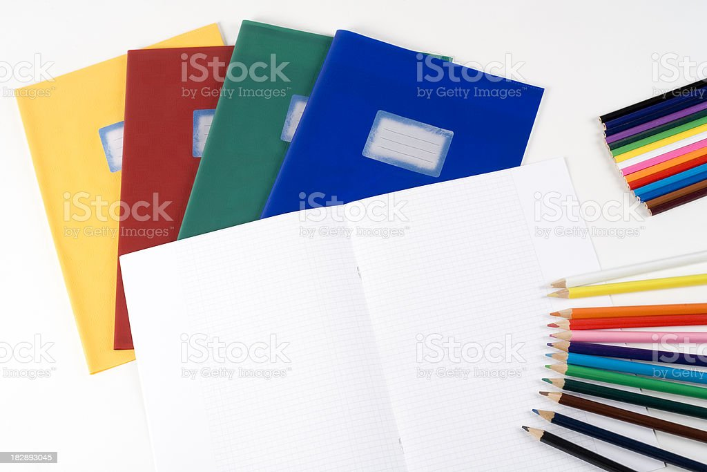 Open exercise book, pencils in various colours royalty-free stock photo